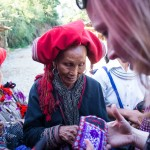 Red Dao women selling embroidered pouches and purses in Sapa, Vietnam