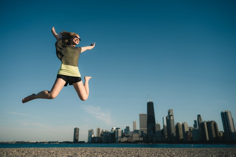 stunning travel portraits: jump shot with city skyline